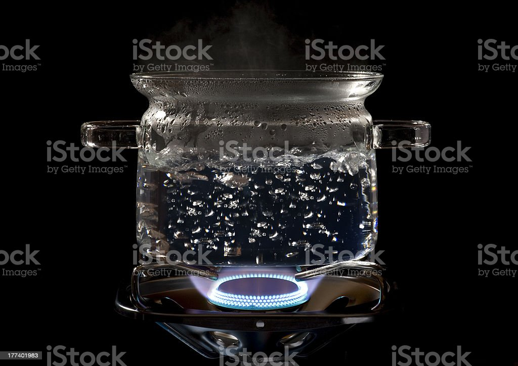 clear cooking pot on a gas stove stock photo