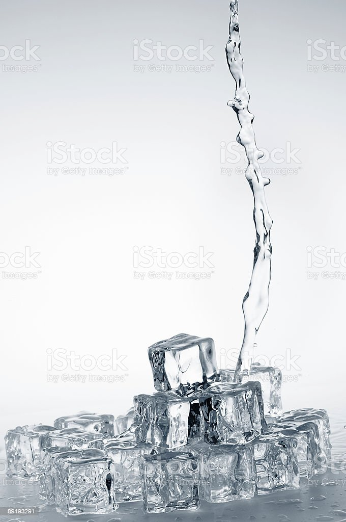 Clear fresh mineral water pouring on frozen crystal ice cubes. royalty-free stock photo