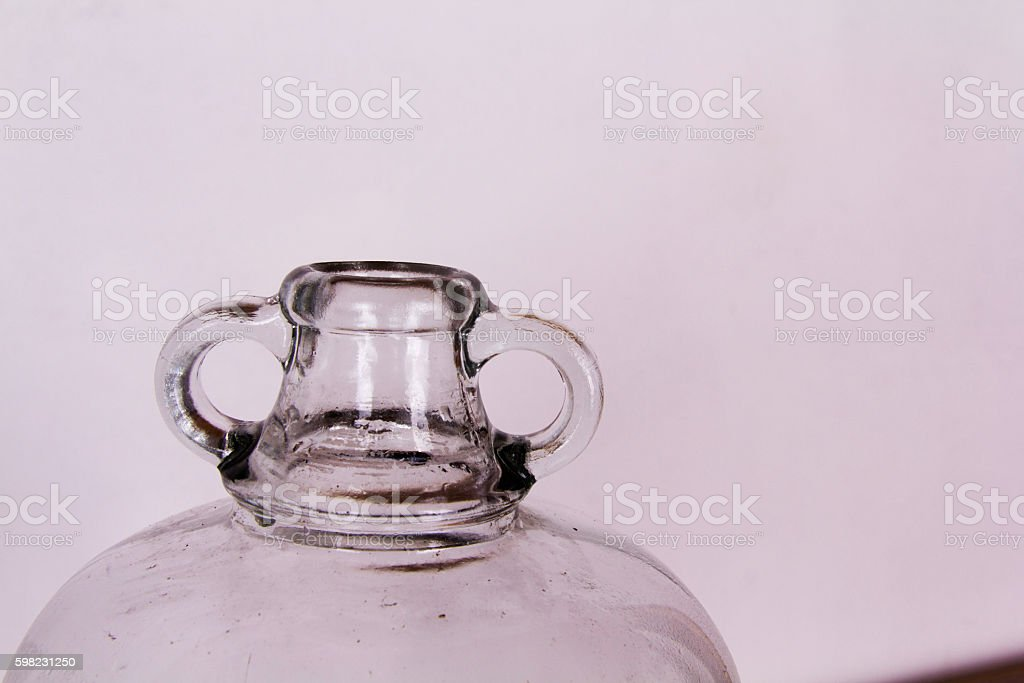 Clear glass demijohn against a light background stock photo