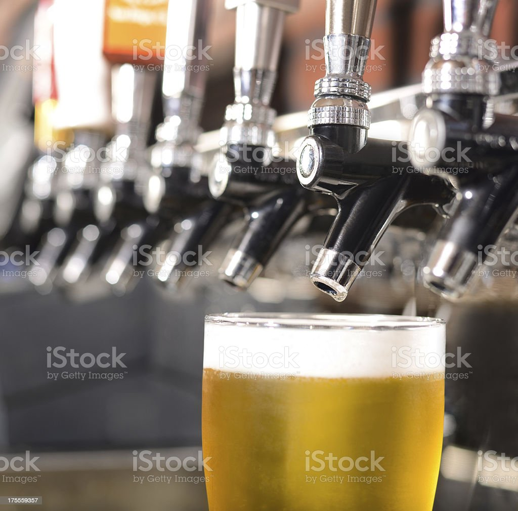 Clear glass of beer under a beer tap stock photo