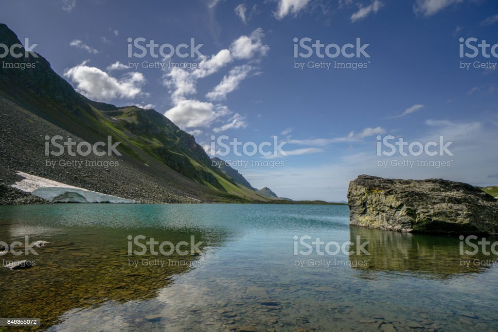 clear mountain lake with large boulder in the foreground stock photo