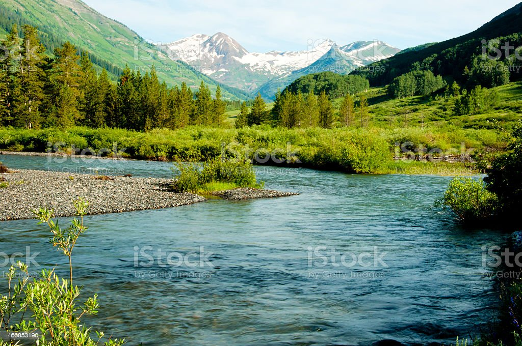 Clear mountain stream and snow capped mountains. stock photo