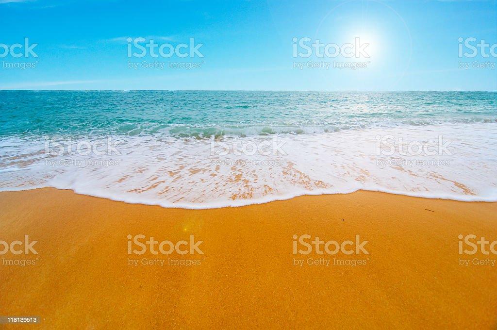 Clear orange sand sunny beach with foamy seashore stock photo