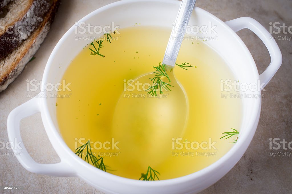 Clear soup with stock at bottom of bowl and parsley floating stock photo