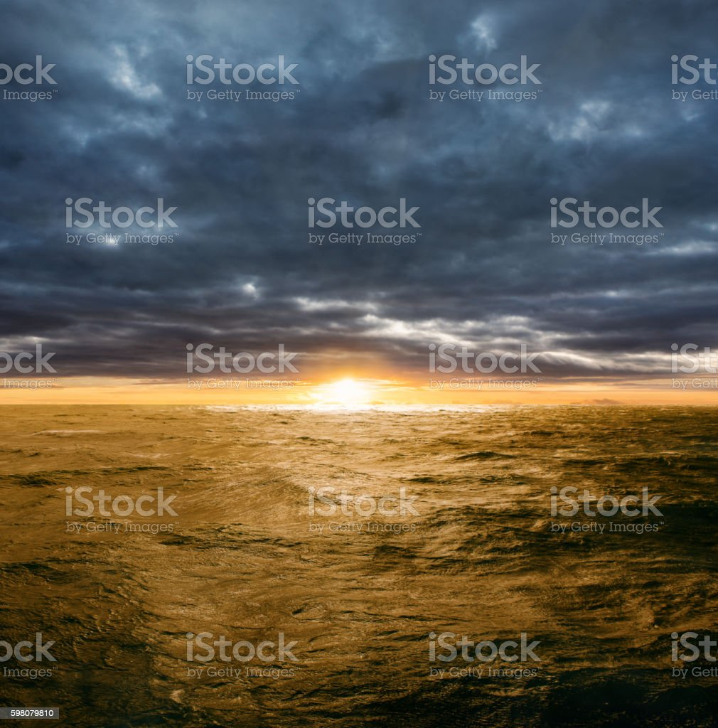 Clearing storm over ocean at sunset stock photo