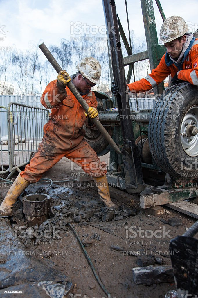 clearing the dril bit of mud next to a borehole stock photo