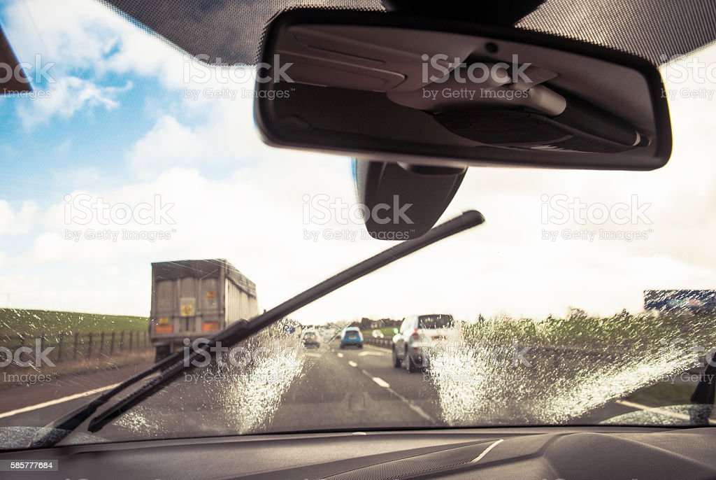 Clearing the windscreen while driving to improve visibility in t stock photo