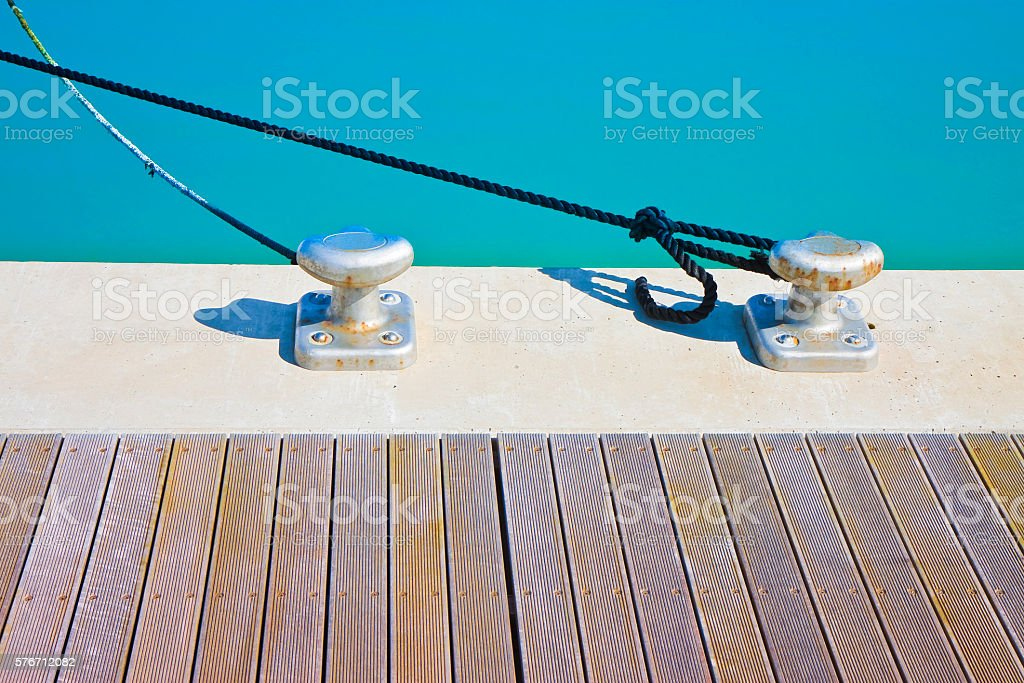 Cleat for mooring boats on wooden platform stock photo
