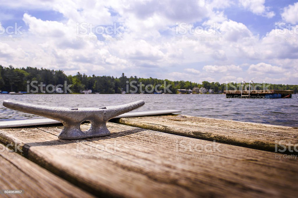 Cleat on a Dock Next to a Pond stock photo