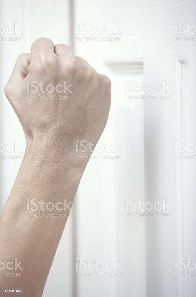 Clenched fist knocking on white door stock photo