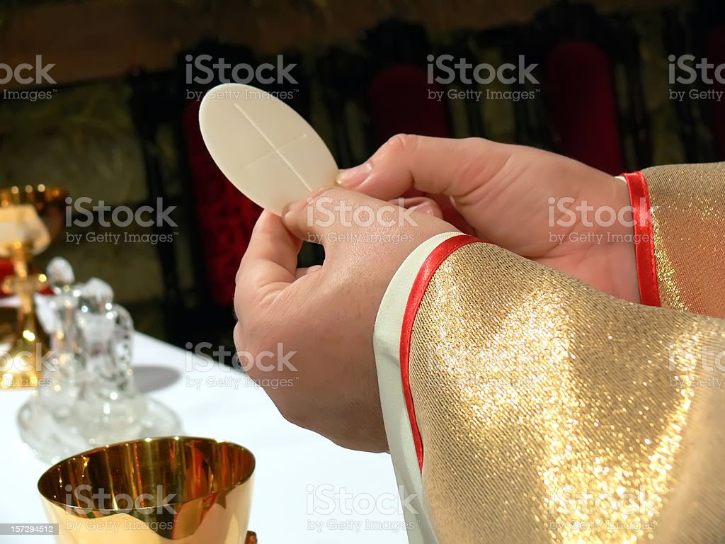 Clergyman hands and communion host stock photo