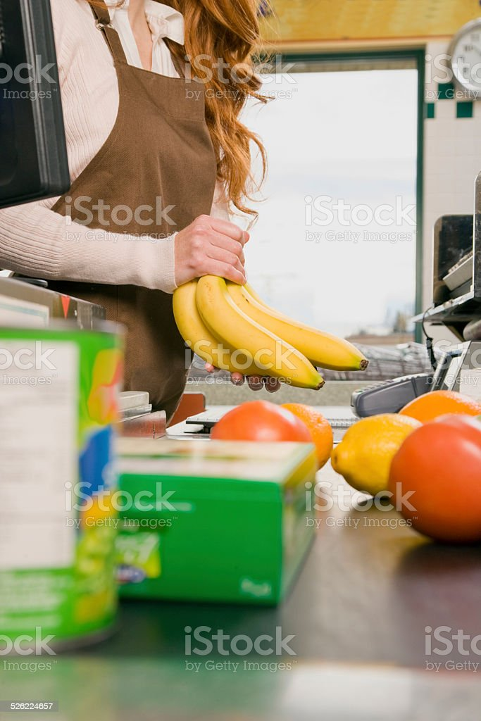 Clerk Pricing Bananas at Checkout in Supermarket stock photo