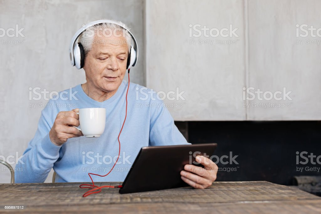 Clever handsome man employing modern technologies in his life stock photo