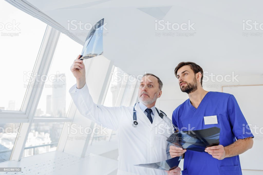 Clever medical specialists discussing radiograph stock photo