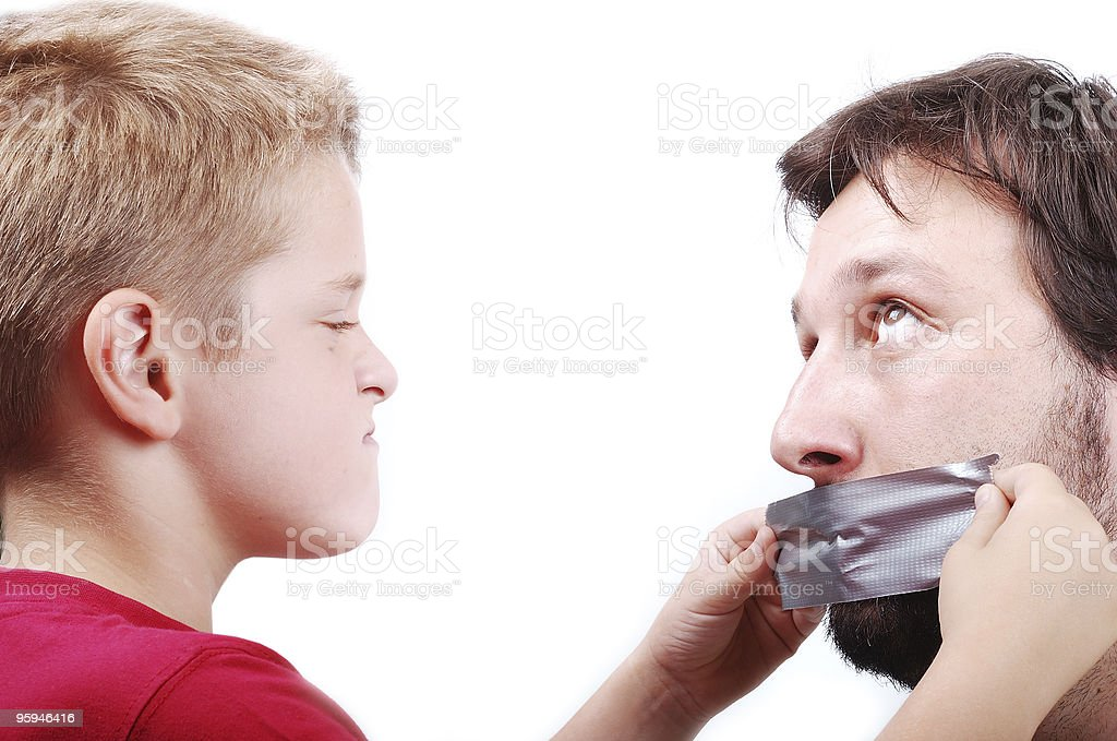 Clever son is putting a strip on father's mouth royalty-free stock photo
