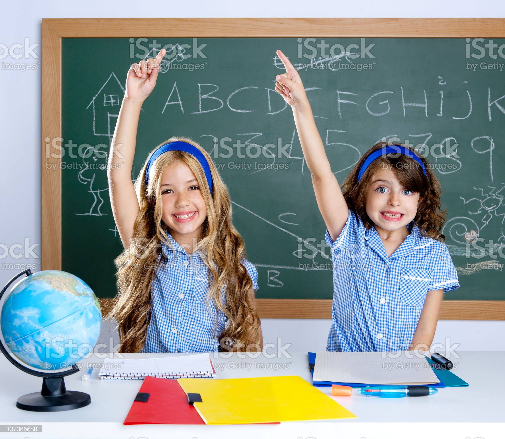 clever students in classroom raising hand royalty-free stock photo