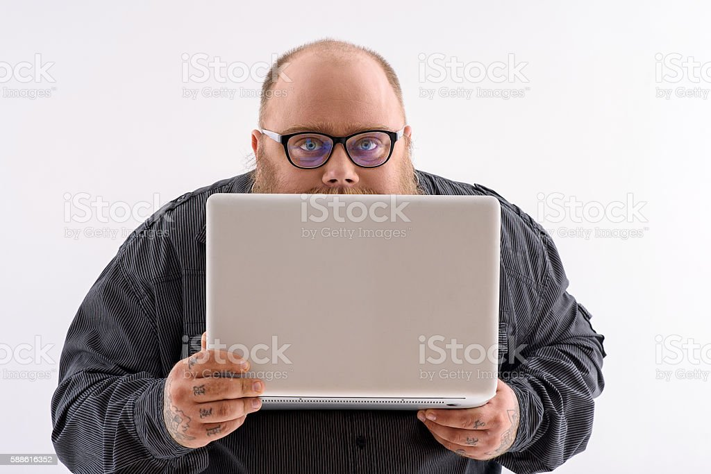 Clever thick guy using computer stock photo