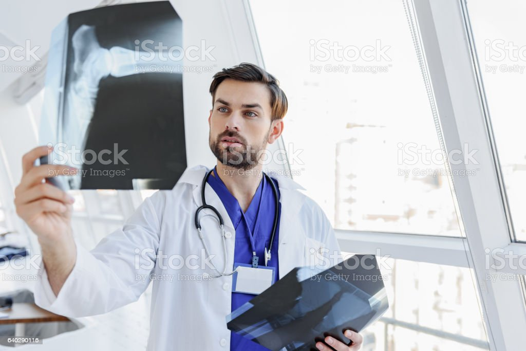Clever young doctor analyzing x-ray photo stock photo