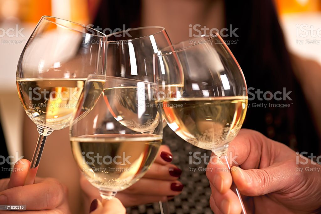 Clicking glasses with white wine. stock photo
