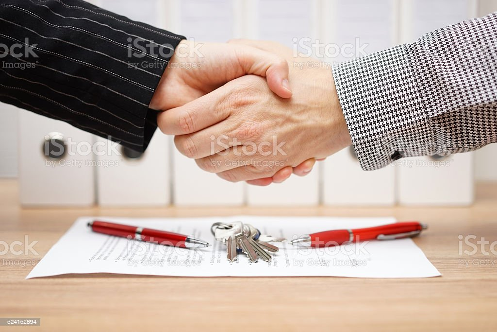 client and agent are handshaking over real estate contract stock photo