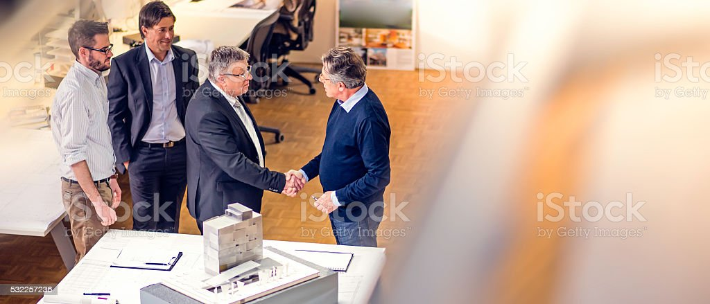 Client and architect shaking hands stock photo