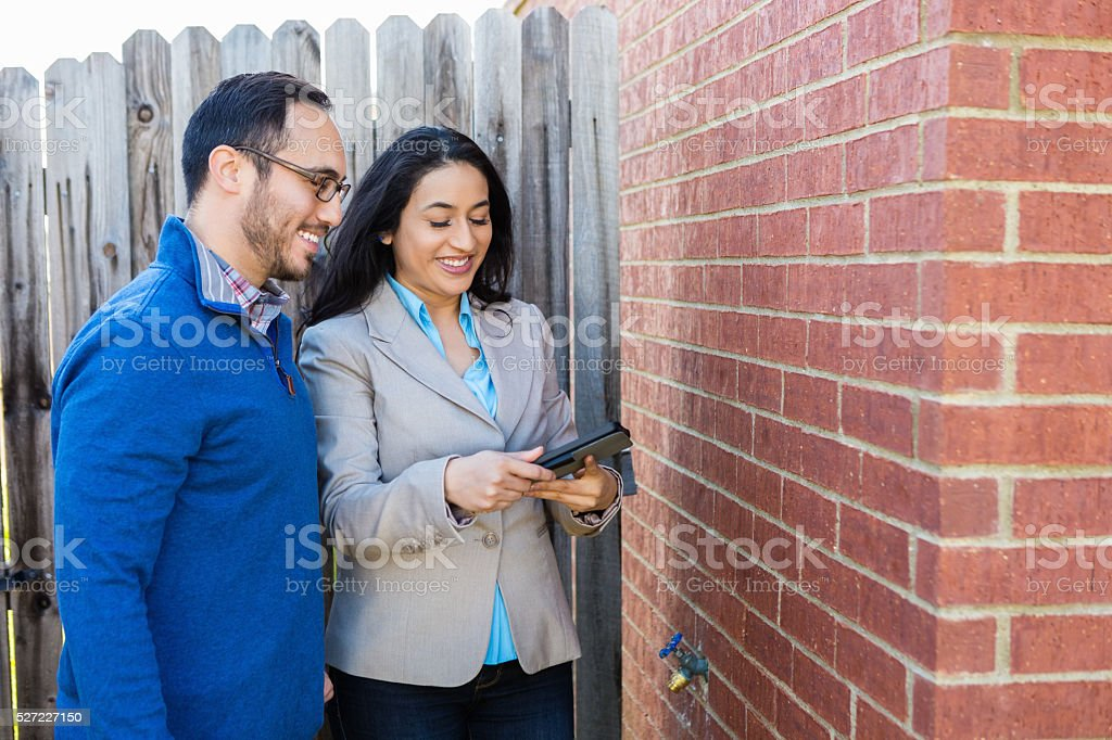 Client and realtor look around ouside of home stock photo