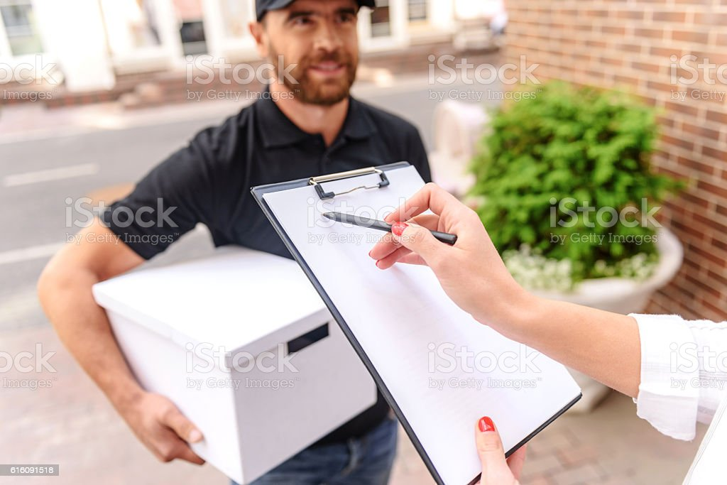client signing a paper outdoors stock photo