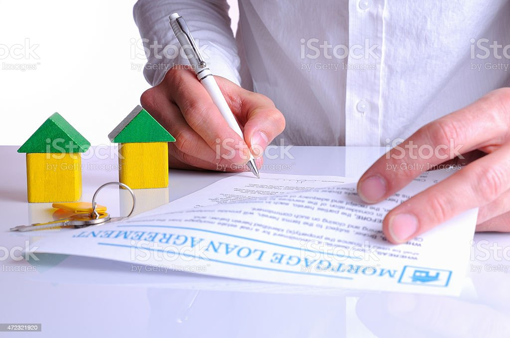 Client signing the mortgage loan agreement with small wooden hou stock photo