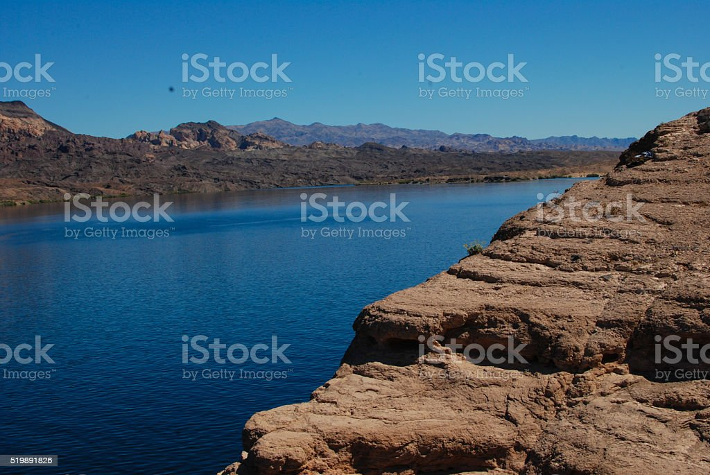 Cliff and blue water at desert lake stock photo