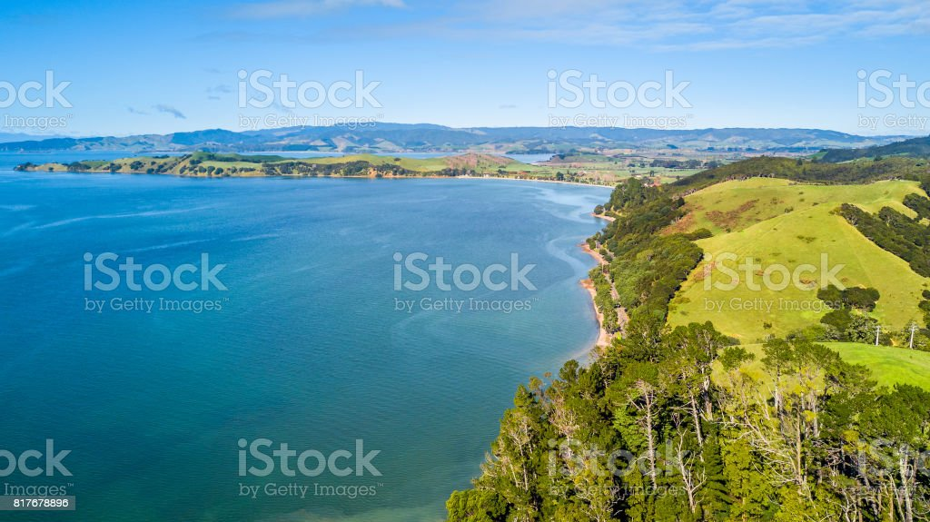 Cliff and sunny beach with farmland on the background. Auckland, New Zealand. stock photo