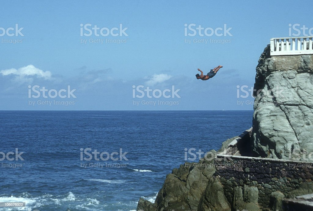 Cliff diver jumping into the ocean stock photo