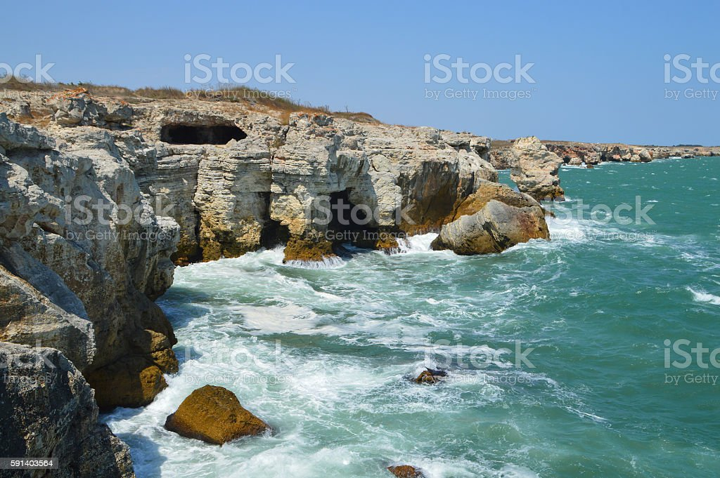 Cliffs with caves above green sea stock photo