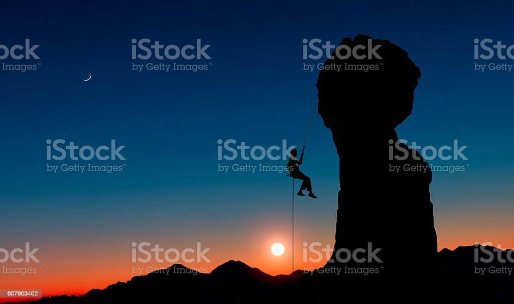 Climber abseiling down from a rocky peak stock photo