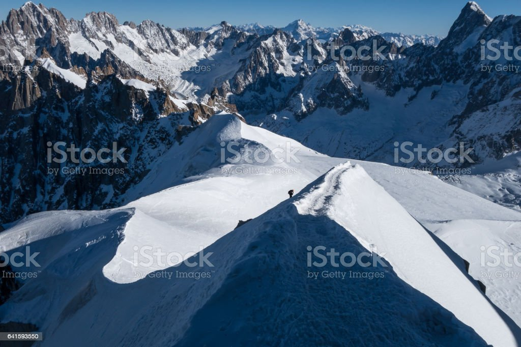 Climber ascending arete in way up to Aiguille du Midi with Vallee Blanche in the background stock photo
