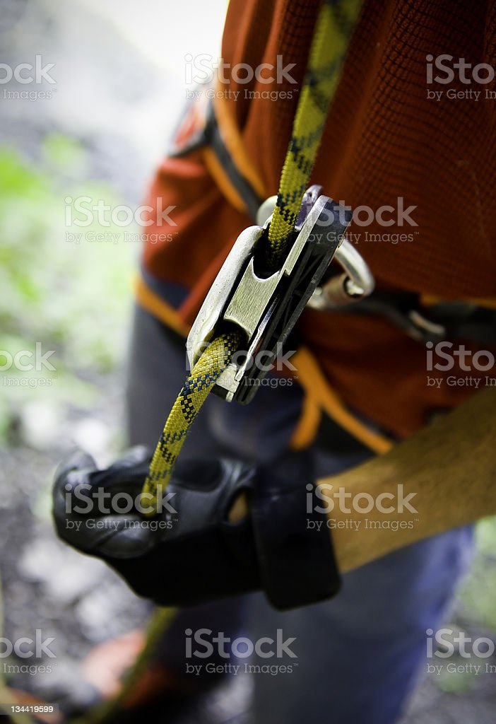 Climber Belaying Closeup of Rope and Belay Device stock photo