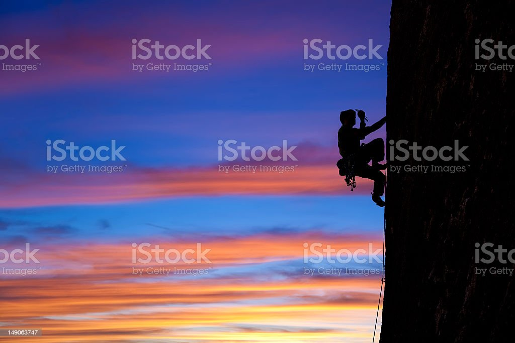 Climber climbing a cliff with multicolored sky stock photo