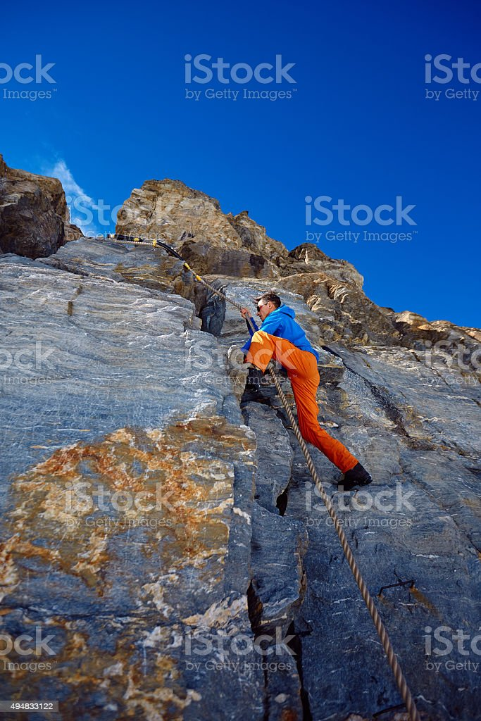 climber climbing up a cliff stock photo