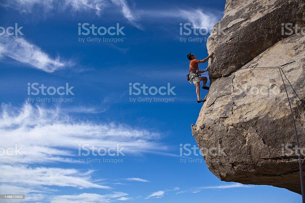 Climber clinging to the edge. stock photo