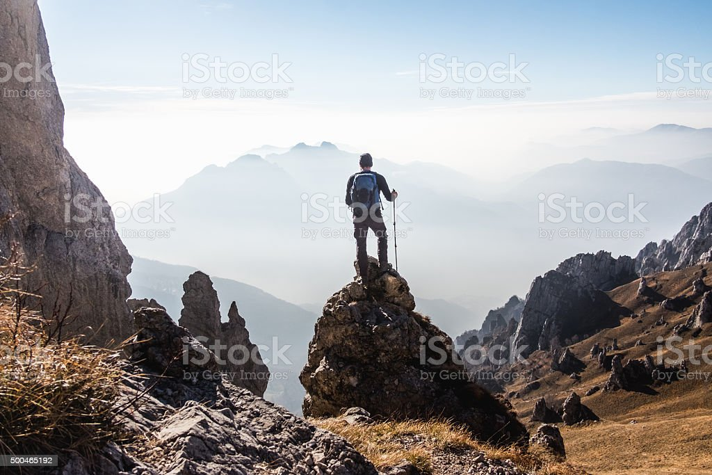 Climber enjoys the view from the top of the mountain stock photo