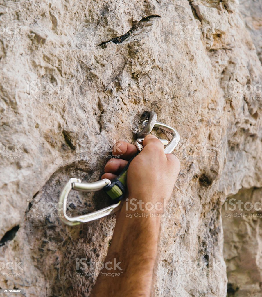Climber holding a quick-draw stock photo