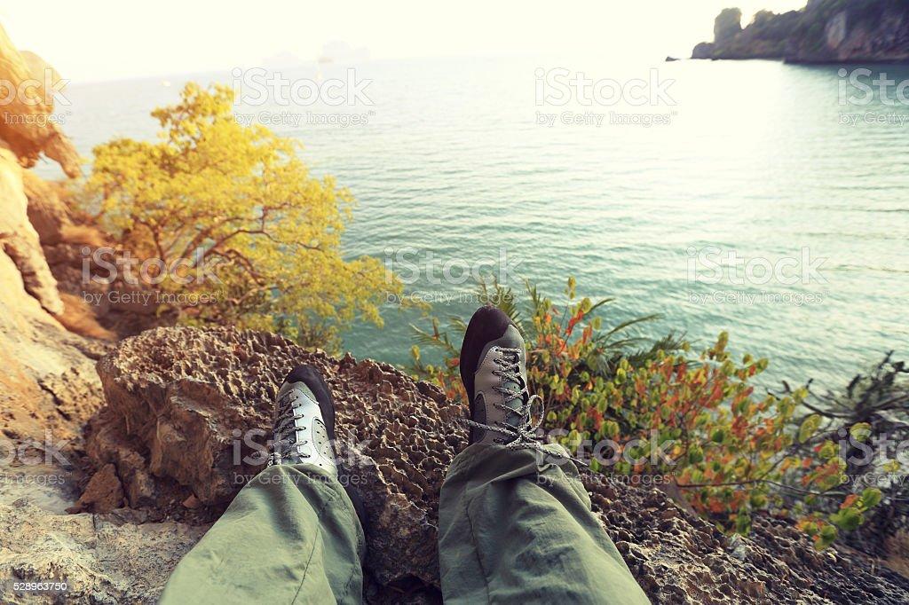 climber legs at seaside rock stock photo