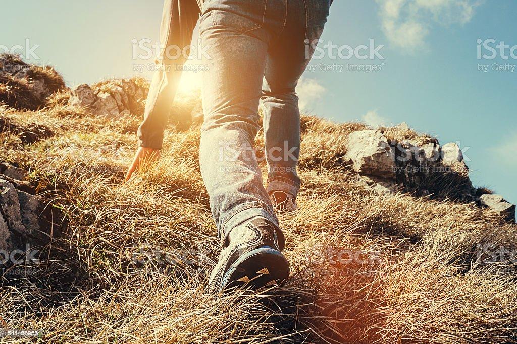 Climber legs make a last steps before peak stock photo