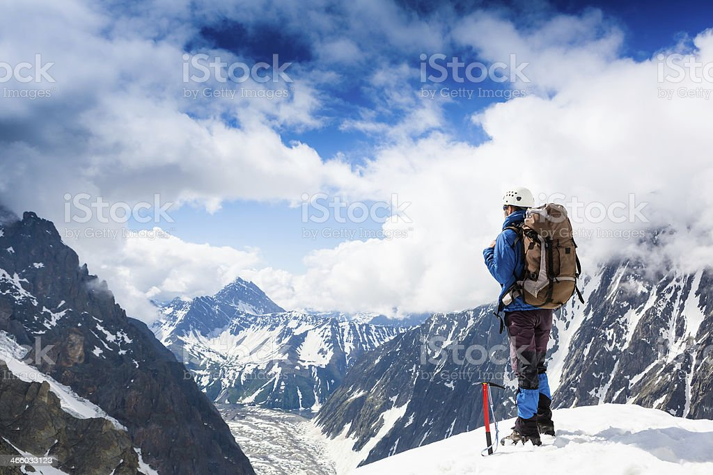 Climber looking Over snow covered mountains stock photo