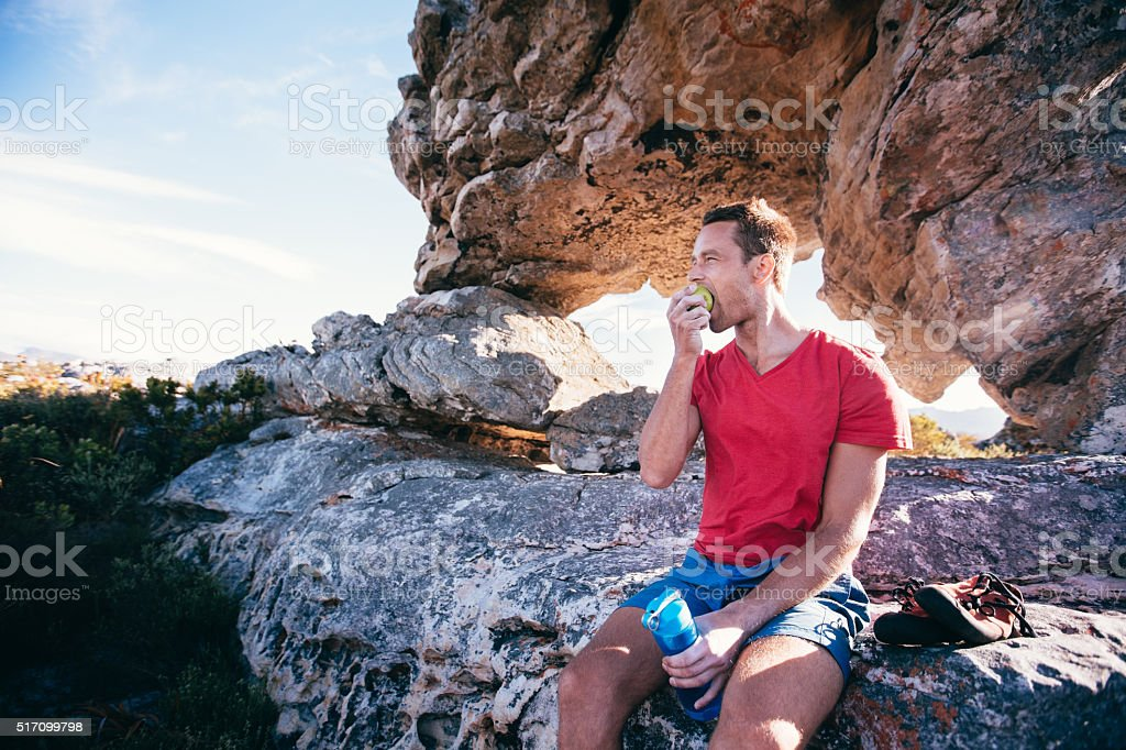 Climber Man eating apple during rest from extreme rock climbing stock photo
