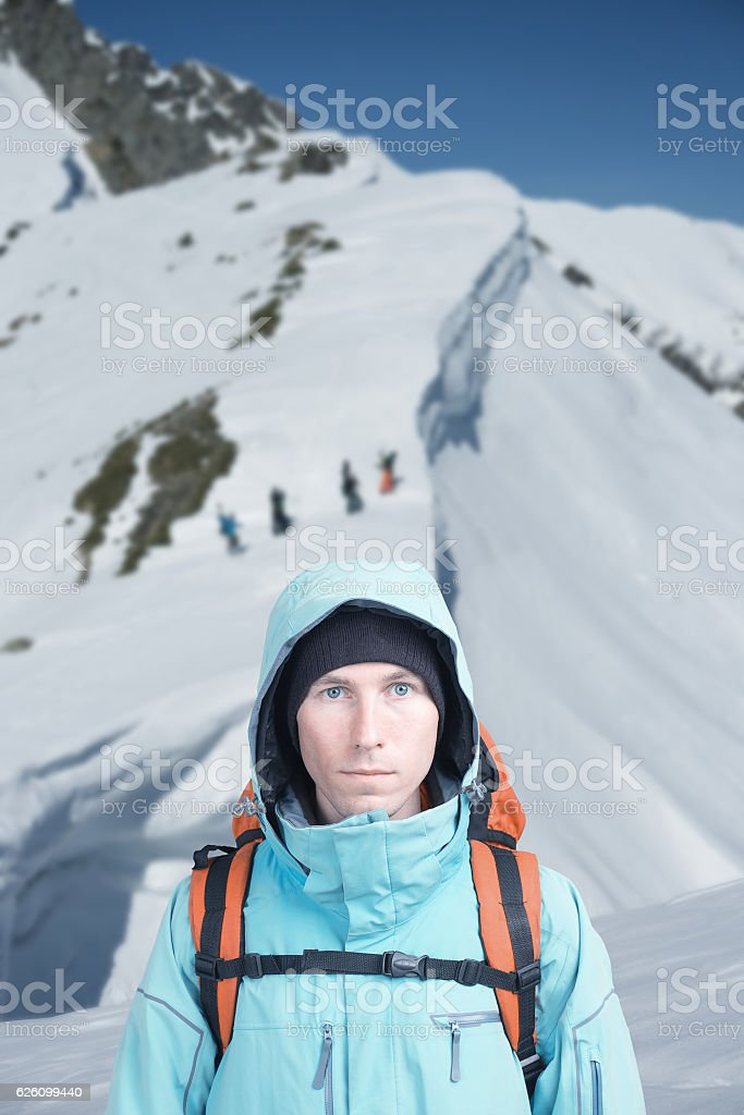 Climber man stands in winter mountains, Snowboarders walking uphill for stock photo