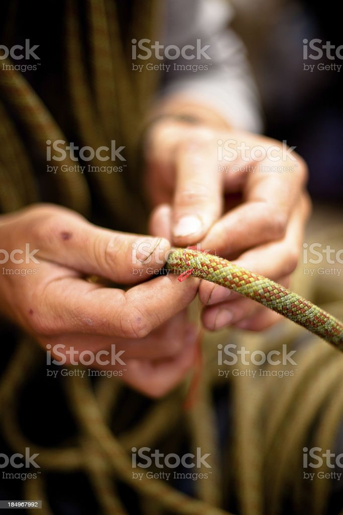 Climber mending his rope royalty-free stock photo