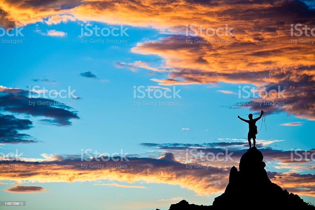 A climber on a mountain summer at sunset stock photo