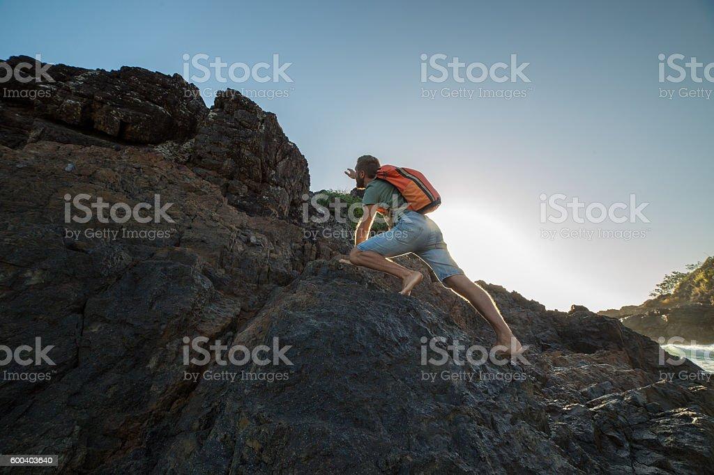 Climber on cliff at sunrise stock photo