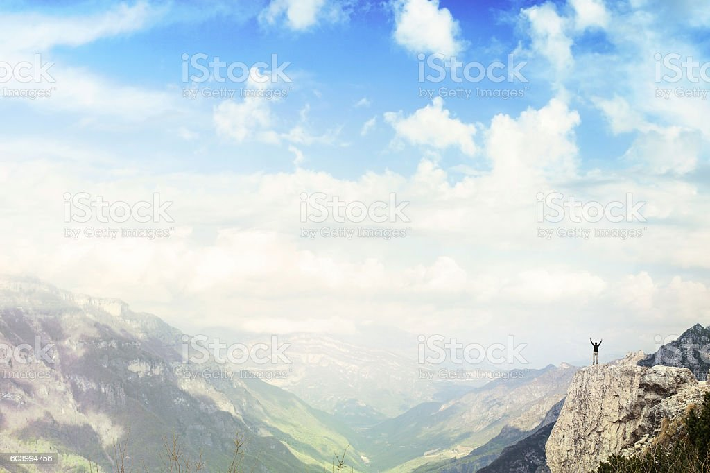 Climber on the top of the mountain exulting stock photo