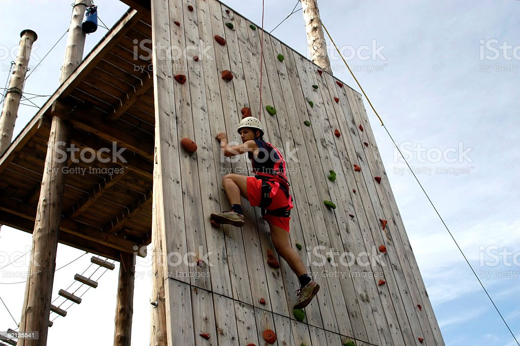 Climber on the wood climbing wall in Amusement Park stock photo